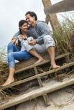 Café potable d'homme de couples asiatiques de femme sur des étapes de plage Photo stock