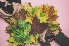 Café potable d'homme et de femme dans des feuilles d'automne Image stock