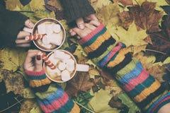 Café potable d'homme et de femme dans des feuilles d'automne Images libres de droits