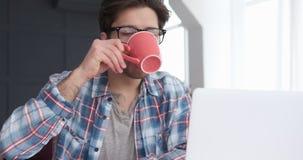 Café potable d'homme fatigué tout en travaillant sur l'ordinateur portable clips vidéos