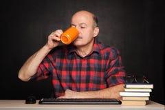 Café potable d'homme plus âgé pendant la coupure Reste de l'étude, Images libres de droits