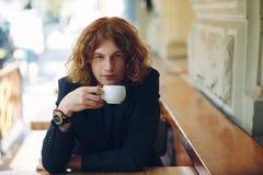 Café potable d'homme rougeâtre à la mode de portrait photos libres de droits