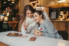 Café potable de belle fille et textoter au téléphone intelligent dans le CAM Image stock