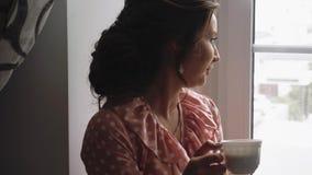 Café potable de belle fille sur le rebord de fenêtre 1 clips vidéos