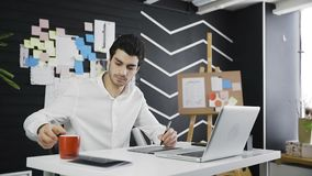 Café potable de concepteur masculin occasionnel et à l'aide de la tablette graphique banque de vidéos