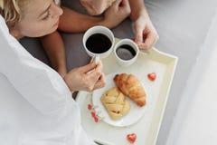 Café potable de couples affectueux voluptueux dans le lit Photographie stock libre de droits