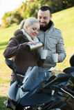 Café potable de couples près de moto Images libres de droits