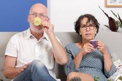 Café potable de couples supérieurs heureux, dans leur sofa Photographie stock
