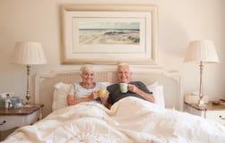 Café potable de couples supérieurs satisfaits ensemble dans le lit Photo libre de droits