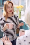 Café potable de femme agréable avec la mère dans la cuisine Photo stock