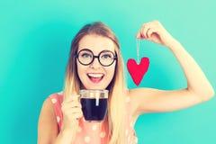 Café potable de femme avec le coussin de coeur photographie stock libre de droits