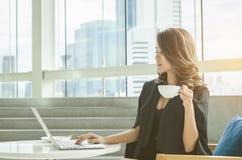 Café potable de femme d'affaires au bureau photographie stock libre de droits