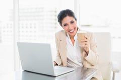 Café potable de femme d'affaires heureuse tout en travaillant sur l'ordinateur portable Photographie stock libre de droits