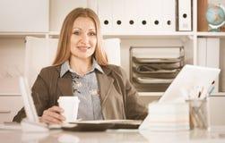 Café potable de femme d'affaires sur l'ordinateur portable photographie stock libre de droits