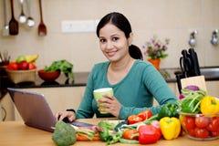 Café potable de femme dans sa cuisine Images libres de droits