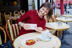 Café potable de femme en café extérieur parisien Image stock