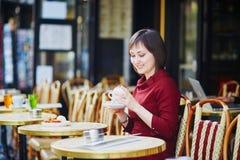 Café potable de femme en café extérieur parisien Photos stock