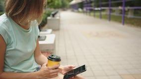 Café potable de femme et regarder le téléphone banque de vidéos