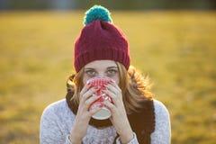 Café potable de femme gaie dans une tasse de Noël Images stock