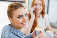 Café potable de femme heureuse avec son ami en café Photos stock