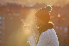 Café potable de femme joyeuse de Noël au coucher du soleil Photos stock