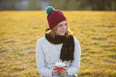 Café potable de femme joyeuse de Noël en parc Photos stock