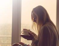 café potable de femme le matin se reposant par la fenêtre Photographie stock