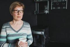 Café potable de femme mûre élégante dans la cuisine Photographie stock