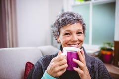 Café potable de femme mûre heureuse à la maison photo libre de droits