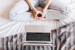 Café potable de femme non reconnue et observation d'une série télévisée sur son ordinateur portable photos libres de droits