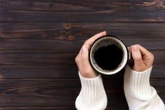 Café potable de femme seule pendant le matin, vue supérieure des mains femelles tenant la tasse de la boisson chaude sur le burea Photographie stock libre de droits