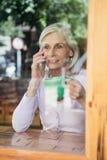 Café potable de femme supérieure tout en parlant au téléphone intelligent Image stock