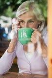 Café potable de femme supérieure tout en parlant au téléphone portable Photographie stock libre de droits