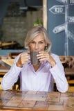 Café potable de femme supérieure tout en se reposant à la table Photo stock