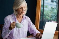 Café potable de femme supérieure tout en travaillant sur l'ordinateur portable à la table Photo libre de droits