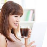Café potable de fille asiatique tout en à l'aide du comprimé photos stock