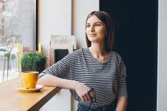 Café potable de fille dans un café Photographie stock libre de droits