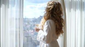 Café potable de fille de beauté Beaux rideaux en ouverture de femme, regardant la fenêtre et appréciant son café de matin banque de vidéos
