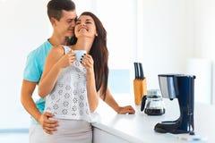 Café potable de fille et son ami l'embrassant dans le kitc Images libres de droits