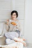 Café potable de fille et un croissant dans le lit photographie stock