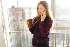 Café potable de jeune belle fille et parler au téléphone, une femme dans un immeuble de bureaux photos stock