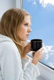 Café potable de jeune belle fille par l'hublot Photo stock