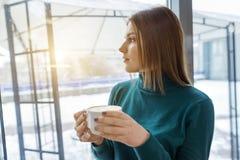 Café potable de jeune belle fille, se tenant dans le profil, regardant la fenêtre Saison d'hiver d'automne dans le café photos libres de droits