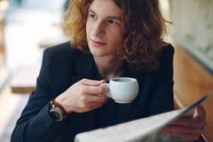 Café potable de jeune entrepreneur rougeâtre tout en lisant photos stock