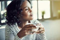 Café potable de jeune femme africaine et regard par une fenêtre image stock