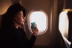 Café potable de jeune femme caucasienne à l'intérieur de la séance d'avion Images stock