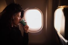 Café potable de jeune femme caucasienne à l'intérieur de la séance d'avion Photographie stock