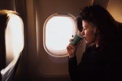 Café potable de jeune femme caucasienne à l'intérieur de la séance d'avion Photos stock