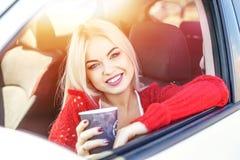 Café potable de jeune femme dans la voiture pendant le matin rire Images stock