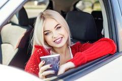 Café potable de jeune femme dans la voiture rire Voyage de concept, Photo libre de droits